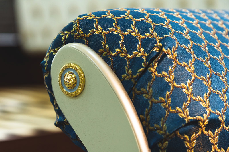 Close-up element of the textile decoration of a soft bedside chair in the bedroom. Luxury furniture in vintage style.