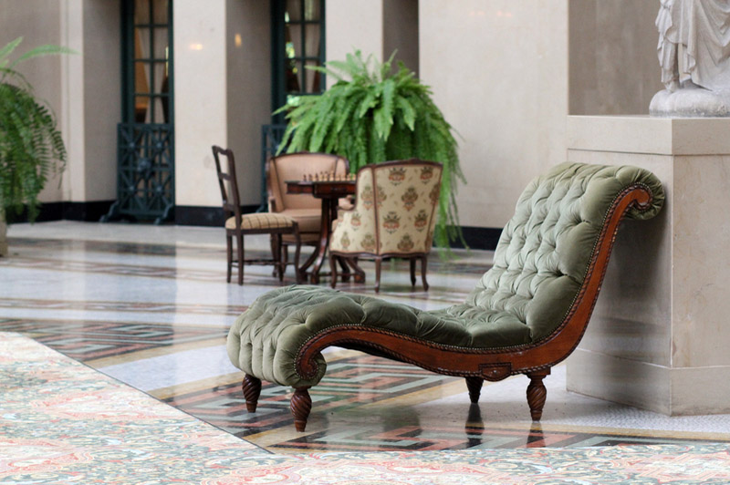 Green suede chaise lounge in a hotel lobby